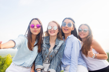 Best friends take selfies while walking in the Park. Four beautiful women wearing sunglasses are having a good day