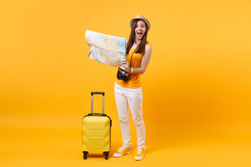 Traveler tourist woman in summer casual clothes, hat with suitcase, city map isolated on yellow orange background. Passenger traveling abroad to travel on weekends getaway. Air flight journey concept. Wall mural