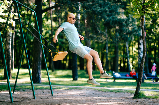 Odd adult bald man in sunglasses jumping from swing on ground in motion.  Childhood behavior. Hulking awkward foolish comic male have fun on children playground outdoor in city park in summer day.