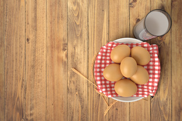 Render of eggs on red towel in ceramic bowl on wooden table with glass of milk. Isolated on white background.