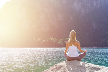 Beautiful woman is doing yoga close to lake. Young girl is practicing yoga and meditating outdoor. Sun salutation series. Padmasana Lotus pose. Sunrise morning light. Spot light. Toned image