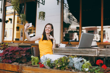 Happy smiling girl in outdoors street coffee shop cafe sitting at table with laptop pc computer doing taking selfie shot on mobile phone in restaurant during free time. Mobile office freelance concept