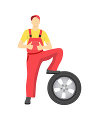 Professional Mechanic in Overalls with New Tire