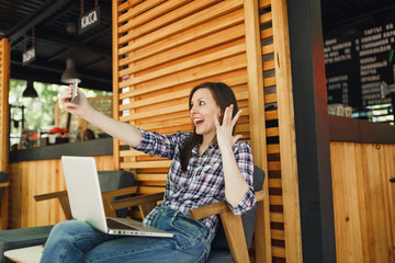 Woman in wooden outdoors street summer coffee shop sitting with laptop pc computer, doing selfie shot on mobile phone, relaxing during free time. Mobile Office. Lifestyle freelance business concept.