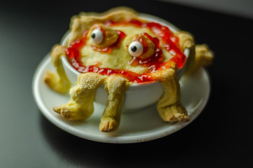 cake baked in the shape of a monster in a ceramic bowl, sweet for Halloween