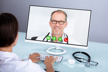 Doctor Video Conferencing With Male Colleague On Computer