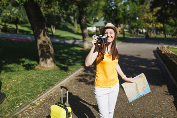 Young traveler tourist woman in hat with suitcase, city map take pictures on retro vintage photo camera in city outdoor. Girl traveling abroad to travel on weekends getaway. Tourism journey lifestyle.