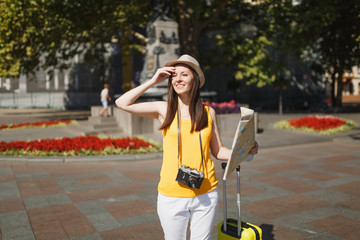 Young beautiful traveler tourist woman in hat with suitcase, city map retro vintage photo camera walking in city outdoor. Girl traveling abroad to travel on weekend getaway. Tourism journey lifestyle.