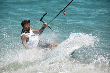 Kitesurfing. The young man is flying on the sea wave on the Board.
