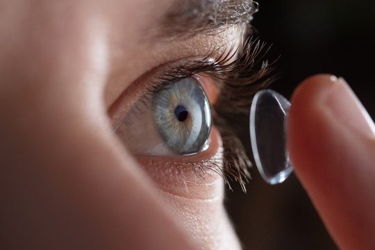Close-up of a man putting contact lenses on blue eye. Concept of: healtcare, optic, hydration of the eye.