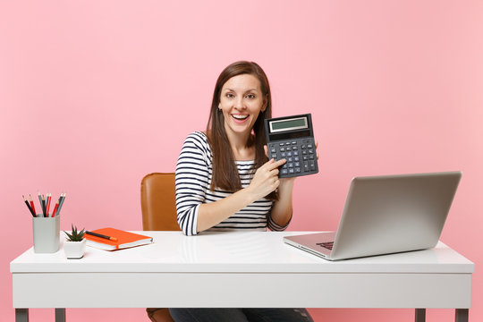 Young joyful woman holding calculator while sitting and working on project at office with contemporary pc laptop isolated on pastel pink background. Achievement business career concept. Copy space.
