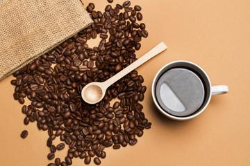 Tuinposter koffiebar Taza de Café junto a granos de café con una cuchara de madera y una bolsa de arpilllera sobre un fondo marrón liso. Vista superior. Copy space
