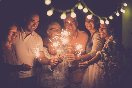 group of caucasian people friends with different ages celebrate together a birthday or new year eve by night outdoor at home. lights and sparkles  with cheerful women and men having fun in friendship