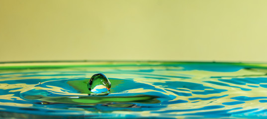 In de dag Kids close up of a water drop falling and impact on a body of water