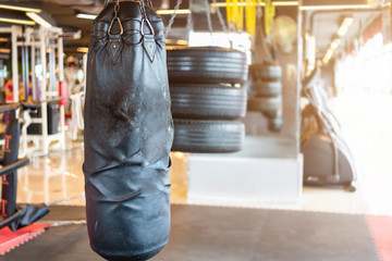 Black punching bag hanging in Abstract blur of defocused boxing gym interior and fitness health club with sports exercise equipment Gym blur background.
