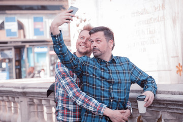 happy gay lifestyle people take a selfie while sight seeing in the city having coffee to go