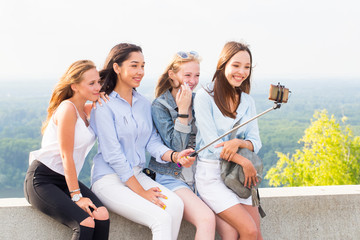 Smiling group of young women taking a selfie in nature