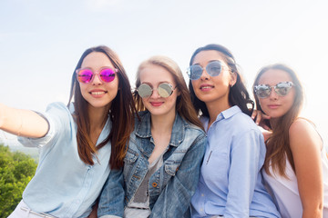 four beautiful young student girl in colorful sunglasses smiling and taking selfies