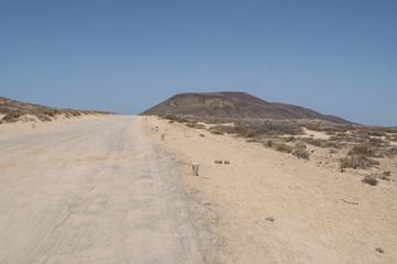 Lanzarote, Isole Canarie: strada sterrata, cespugli e paesaggio desertico con la Montagna Pedro Barba, il vulcano dell'isola La Graciosa