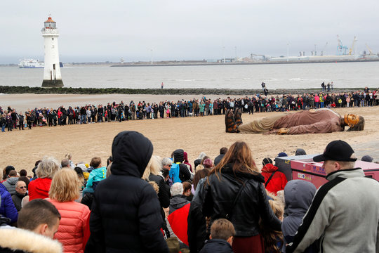 People look at one of Royal Deluxe's giant marionette puppets as it lies on the beach at New Brighton