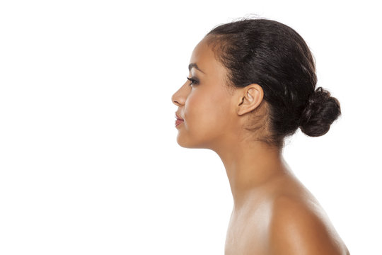 profile of young beautiful dark-skinned woman with bun on a white background
