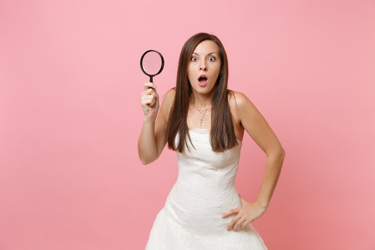 Portrait of shocked bride woman in white lace wedding dress holding magnifying glass isolated on pastel pink background. Wedding to do list. Organization of celebration. Copy space for advertisement.