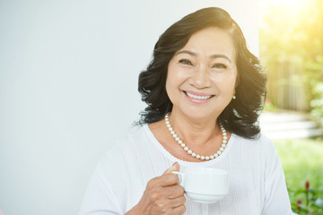 Waist-up portrait of beautiful senior Asian woman with pearl necklace holding cup of tea and smiling at camera cheerfully