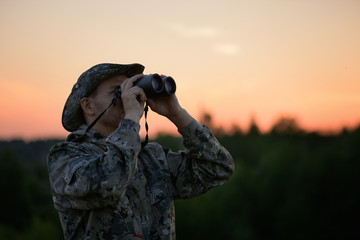 The caucasian man is wearing a camouflage suit watching through binoculars in outdoors. The birdwatcher with field glasses is in a twilight in rural.