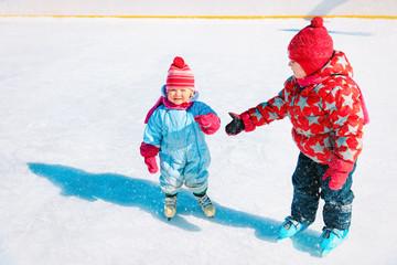 little girls skating together, kids winter sport