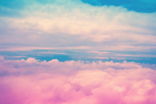Dreamy pink and blue sky above white clouds. Colorful cloudscape background