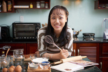 Portrait of young pretty Asian woman standing at kitchen counter with cookware, holding whisk and smiling at camera joyfully