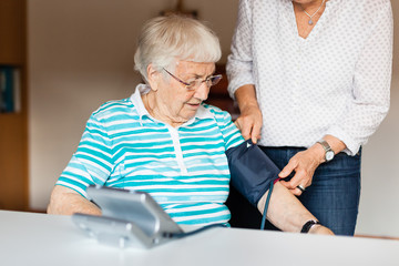 Senior woman measuring blood pressure at home with help of other woman