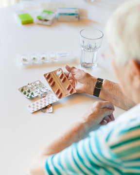 Senior woman holding medicine and pills in her hand