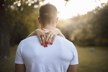 Woman holding hands on neck of her boyfriend.