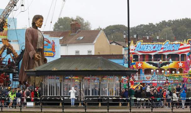 One of Royal Deluxe's giant marionette puppets stands in a fairground in New Brighton