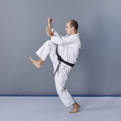 On a gray background, a young active athlete performs formal karate exercises.