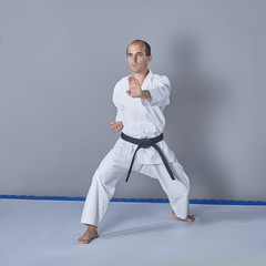On a gray background, a young active athlete trains formally karate exercises.