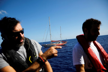 British-flagged NGO Proactiva Open Arms rescue boat Astral is seen in the background as Erasmo Palazzotto and Riccardo Gatti discuss onboard the Italian-flagged rescue vessel Mare Jonio, in the central Mediterranean Sea