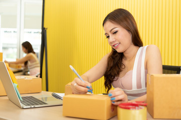 Beautiful of Asian woman is taking note on purchase orders while sitting over yellow wall.