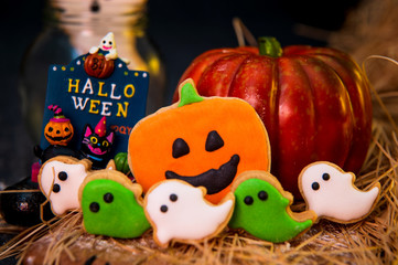 Fresh homemade decorated halloween cookies and sweets on dark background, concept of halloween monster party, copy space, close up
