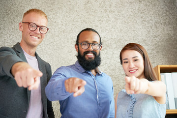 Portrait of successful young business team pointing at camera and smiling