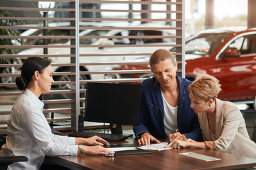 Sales agent at the table desk telling about car features to cheerful couple of customers at car dealership office