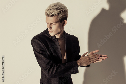 Handsome stripped blonde male model wearing black suit on