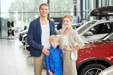 automobile sales centre. young family with child boy in car selling club