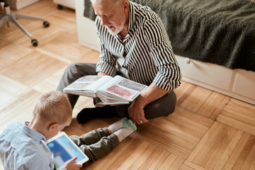 grandfather reminisces about his youth, watching photo album, while his grandson playing on digital tablet