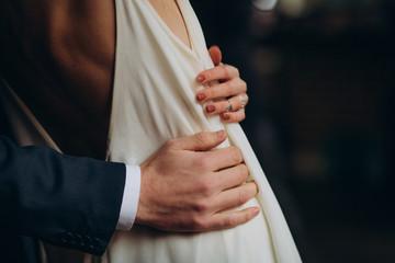 bride groom close together holding hands hugging