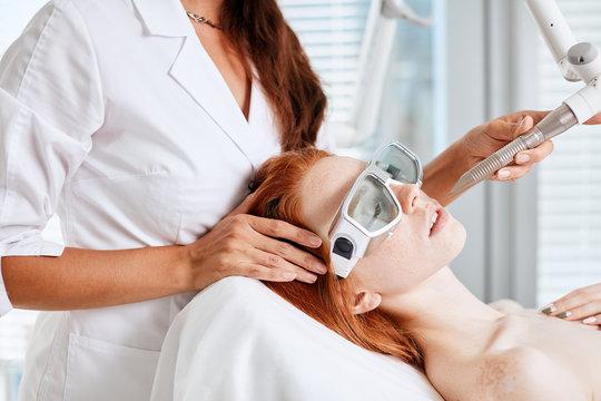 Woman getting laser face treatment in medical spa center, skin rejuvenation concept