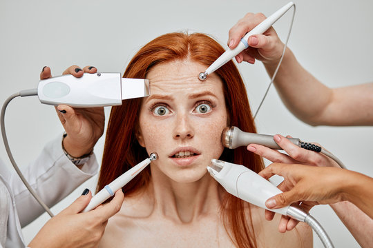 Several beauticians doing cosmetology procedures using medical tools all together at the same time on scared and shocked female face. Reactions, side effects after cosmetology procedures Concept