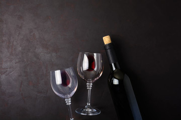 Two wineglasses and wine bottle lying on dark wooden background. Top view. Flat lay. Copy space
