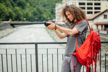 Portrait of happy young man, tourists with camera in city.